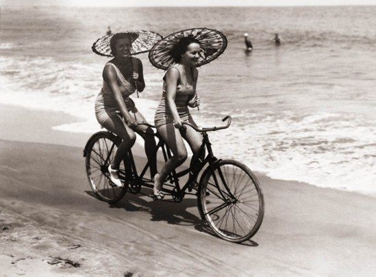 ca. 1910, USA --- Two women in swimwear enjoy a tandem bike ride down the beach with parasols in hand. --- Image by © Underwood & Underwood/Underwood & Underwood/Corbis